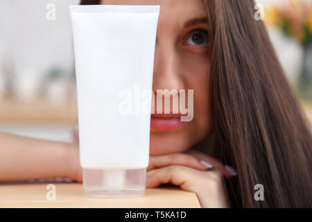 Portrait beautiful long hair young girl holding skincare cosmetics, tubes with face cream, body mask, serum, lip balm, regenerating shampoo. Place for - Stock Photo