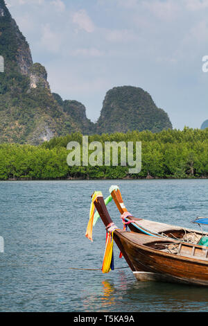 Long tail wooden boat moored at Railey beach in Krabi province, Thailand. Vertical orientation - Stock Photo