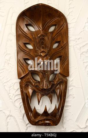 Wood carved Hawaiian Tiki mask of multi eyed demon on stucco wall - Stock Photo
