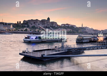 BUDAPEST / HUNGARY - 04.21.2019: Panoramic view of Buda Castle, with tourist boats on Danube river in the foreground. - Stock Photo