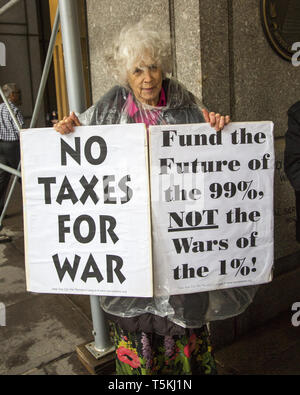 Long time committed peace and anti-war activists demonstrate and educate passersby on Tax Day, April 15th,  in front of the Internal Revenue Service offices on Broadway in downtown Manhattan telling Americans to withhold their tax money from military use. - Stock Photo