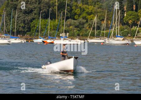 GARDA, LAKE GARDA, ITALY - SEPTEMBER 2018: Small fishing boat returning to the harbour at Garda. - Stock Photo