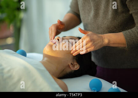 Woman receives facial cupping massage facial rejuvenation at acupuncture wellness spa - Stock Photo
