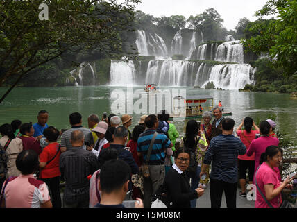(190425) -- NANNING, April 25, 2019 (Xinhua) -- Tourists visit Detian Waterfalls scenic area in Daxin County, south China's Guangxi Zhuang Autonomous Region, April 17, 2019. Guangxi has promoted major tourism projects and brands in recent years, and the customs of border area have attracted a lot of tourists. (Xinhua/Lu Boan) - Stock Photo