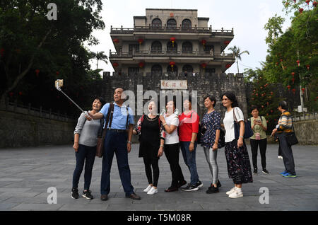 (190425) -- NANNING, April 25, 2019 (Xinhua) -- Tourists pose for photos at Friendship Pass of Pingxiang City, south China's Guangxi Zhuang Autonomous Region, April 18, 2019. Guangxi has promoted major tourism projects and brands in recent years, and the customs of border area have attracted a lot of tourists. (Xinhua/Lu Boan) - Stock Photo
