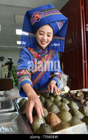 (190425) -- NANNING, April 25, 2019 (Xinhua) -- A staff member arranges glutinous rice dumplings at Equan scenic spot in Jingxi City, south China's Guangxi Zhuang Autonomous Region, April 16, 2019. Guangxi has promoted major tourism projects and brands in recent years, and the customs of border area have attracted a lot of tourists. (Xinhua/Lu Boan) - Stock Photo