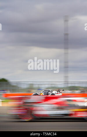 Action shot of Porsche 911 race car seen behind a blur of another race car in the foreground, WEC 6 Hours of Silverstone 2018 - Stock Photo