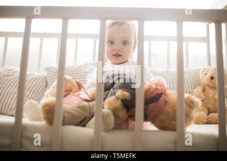 The toddler sits in a crib and plays among pillows and teddy bears.