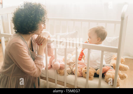 Happy mother sits next her baby with toys in the crib.