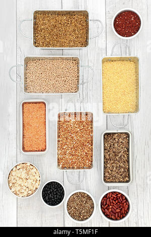 Dried health food for liver detox  with grains, seeds, cereals and legumes in metal dishes on rustic white wood background. - Stock Photo