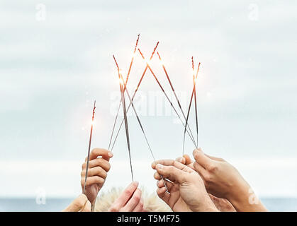 Close up hands of group of happy friends having fun celebrating with sparklers fireworks outdoor - Youth, celebrate, party lifestyle concept - Stock Photo