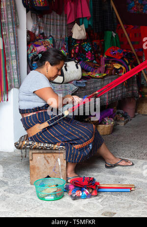 Guatemala lifestyle, local guatemalan woman weaving colorful textiles, Antigua Guatemala Central America - Stock Photo
