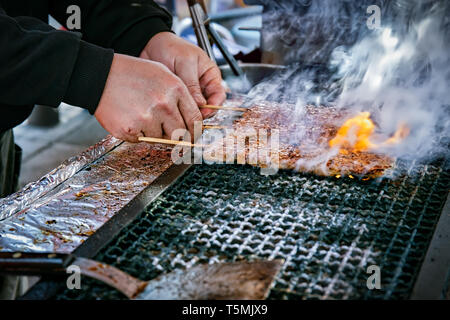 Meat on a stick cooking on a grill in Yokosuka, Japan. - Stock Photo