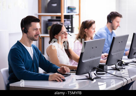 Happy Young Customer Service Executives Using Earphones Working In Call Center - Stock Photo