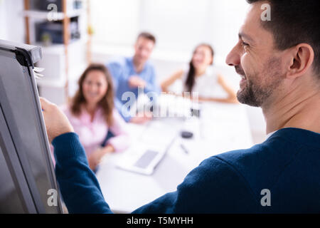 Close-up Of Young Businessman Giving Presentation To His Coworker In Office - Stock Photo