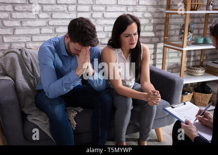 Psychologist Talking With Depressed Young Couple About Mental Condition In Home - Stock Photo