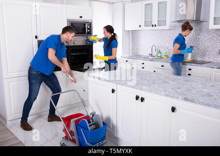 Group Of Young Janitors In Uniform Cleaning Kitchen At Home - Stock Photo