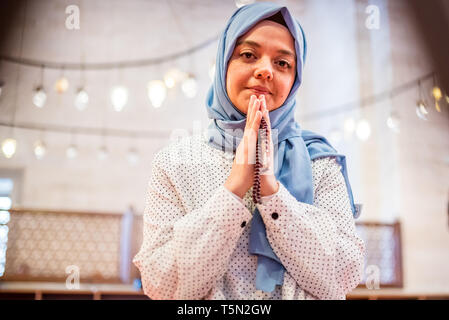 Muslim woman in headscarf and hijab prays while clasping her hands with mosque on background.Religion praying concept. - Stock Photo