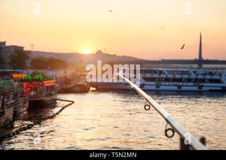 Fishing rod at Galata bridge with view to ships at sunset in Istanbul, Turkey - Stock Photo