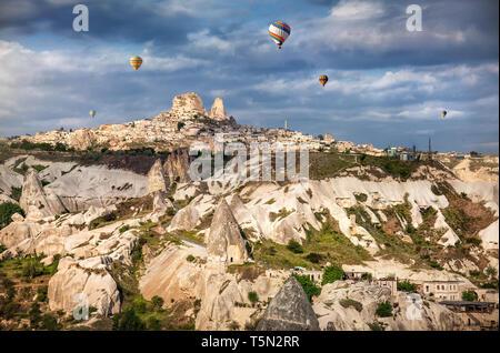 Hot air balloons flying over Cappadocia near Uchisar castle at sunrise, Turkey - Stock Photo