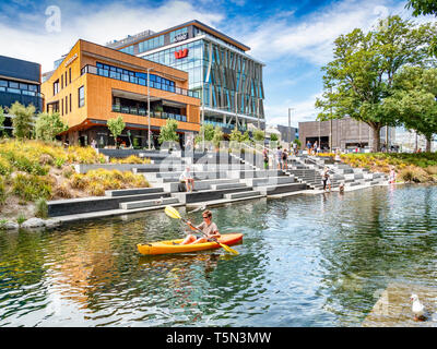3 January 2019: Christchurch, New Zealand - A man in a kayak passes in front of The Terrace, a newly built entertainment complex on the banks of the... - Stock Photo
