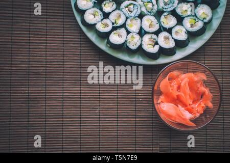 Homemade sushi with ginger on wooden rug - Stock Photo