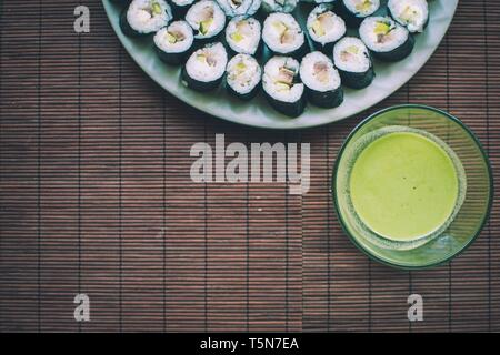 Homemade sushi with wasabi sauce on wooden rug - Stock Photo