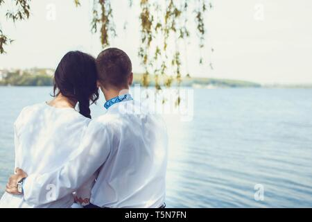 Lovely couple sitting on the bench and looking on the lake in ukrainian traditional clothes - Stock Photo