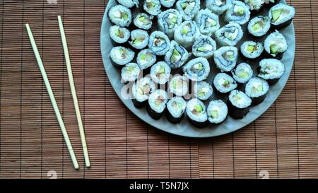 Homemade sushi with sushi sticks on wooden rug - Stock Photo