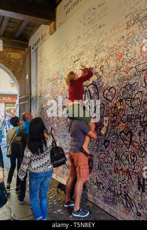 Verona, Italy - October 20, 2018: Couple writes love messages on the wall in Juliet house or Casa di Giulietta - Stock Photo