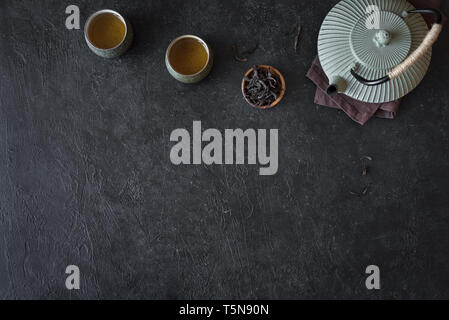 Teapot and Teacups on black background, copy space. Traditional Asian Tea Set -  iron teapot and ceramic teacups with green tea for tea ceremony. - Stock Photo