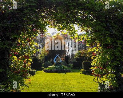The White garden and sculpture at Chenies Manor, Buckinghamshire in April sunshine beautiful fresh green lawn, framed with akebia, Chocolate Vine. - Stock Photo