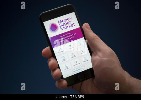 A man looks at his iPhone which displays the Money Supermarket logo (Editorial use only). - Stock Photo