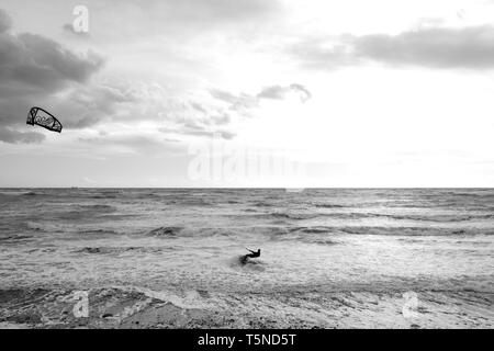 A Kitesurfer in strong winds surfing out of the breakers through the surf at Brook beach on the Isle of Wight. - Stock Photo