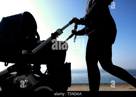 A woman pushing a pram or buggy out for a walk by the seaside partly in silhouette with the sea horizon and blue sky in the background. - Stock Photo