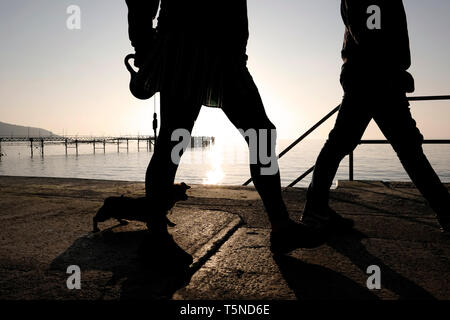 Walking the dog along the promenade revetment walkway between Totland and Colwell Bays.Two walkers in silhouette with a setting sun over Totland Pier. - Stock Photo