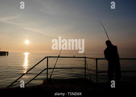 Angling fisherman using rods to beach cast from the walkway above Totland Bay as the sun sets over the distant horizon and Totland Pier. - Stock Photo
