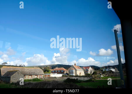 An idyllic English countryside farm and hamlet scene view from a passing bus window. Blue sky and fluffy white clouds look like steam train puffs. - Stock Photo