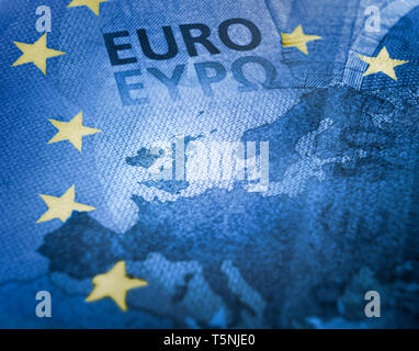 Brexit concept. Unfocused Euro bill close up detail of Europe map with focus on Great Britain. European Union colors flag with yellow stars - Stock Photo