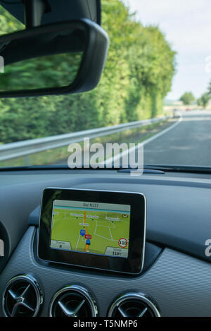 GPS unit in a Mercedes on  road in France. - Stock Photo