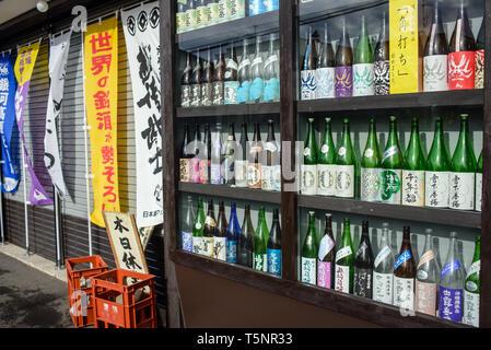 Showcase with sake bottles on the street of Abashiri, Hokkaido, Japan - Stock Photo