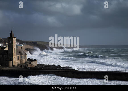 Sunlight picks out the buildings against dark threatening skies as  crashing waves batter the coast at Porthleven as the storm passes. Cornwall - Stock Photo