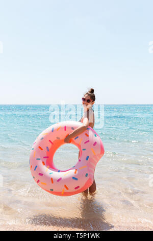 A woman walks into the sea water. Girl relaxing on inflatable ring on the beach. Summer holidays and vacation concept. - Stock Photo