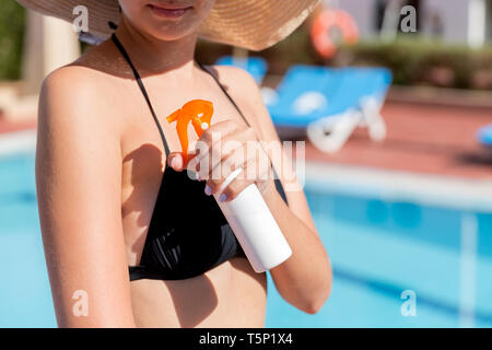 Beautiful woman protecting her skin against sunburn, applying sun lotion on her shoulder by the pool. Sun Protection Factor in vacation, concept. - Stock Photo