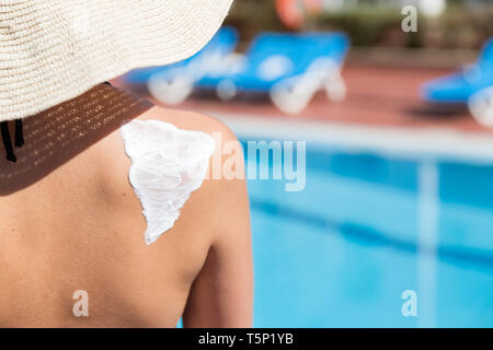 Woman in hat is applying sun cream on her shoulder by the pool. Sun Protection Factor in vacation, concept. - Stock Photo