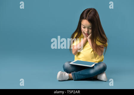 surprised cute little child girl holding blank tablet computer on blue background