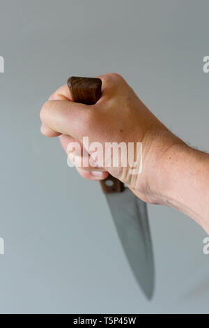 Man's hand with a knife on gray background. Concept of violence. Hand of a gangster with a knife. vertical photo. - Stock Photo