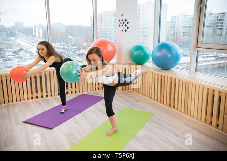 Two young women balancing on one leg holding a ball in the fitness studio - Stock Photo