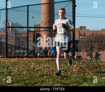 West Islip, NY, USA - 24 November 2017: The winner of a local turkey trot exits the road heading toward the track and the final 400 meters. - Stock Photo