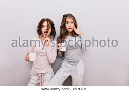 Two pretty girls in pajamas fooling around on gray wall background. They having fun to camera - Stock Photo